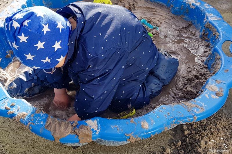 Kind spielt im matschigen Sandkasten