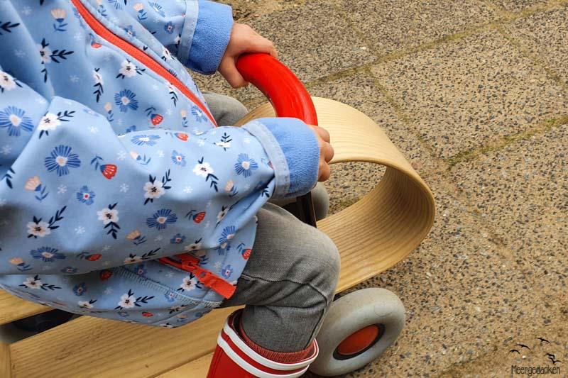 Ein Kleinkind in einer blauen Jacke und mit roten Gummistiefeln auf einem Rutscheauto aus Holz.